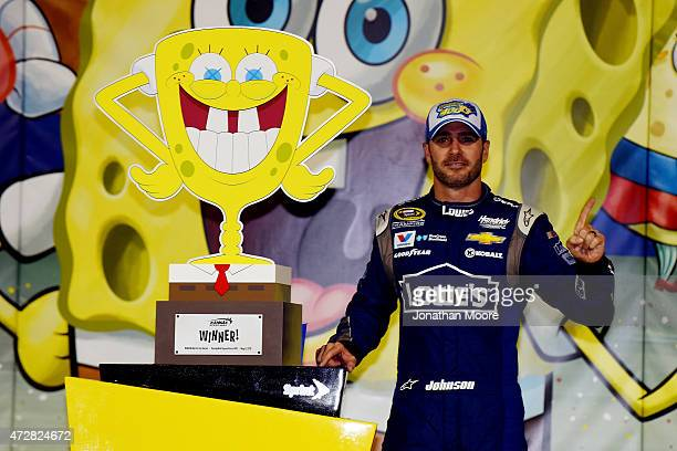 Jimmie Johnson driver of the Lowe's Chevrolet poses with the trophy in Victory Lane after winning the NASCAR Sprint Cup Series SpongeBob SquarePants...