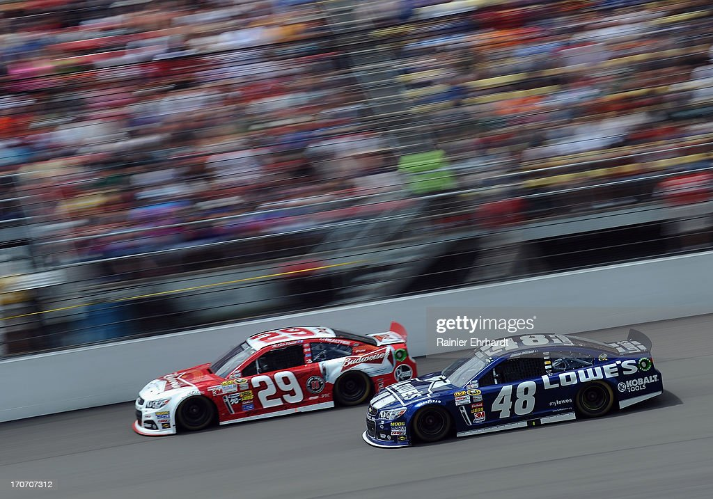 Jimmie Johnson, driver of the #48 Lowe's Chevrolet, races Kevin Harvick, driver of the #29 Budweiser Chevrolet, during the NASCAR Sprint Cup Series Quicken Loans 400 at Michigan International Speedway on June 16, 2013 in Brooklyn, Michigan.