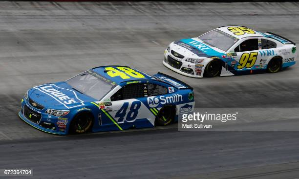 Jimmie Johnson driver of the Lowe's Chevrolet races Michael McDowell driver of the WRL General Contractors Chevrolet during the Monster Energy NASCAR...