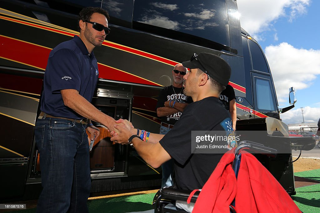 Jimmie Johnson (L), driver of the #48 Lowe's Chevrolet, shakes hands with Marc Fucarile, who was the last Boston Marathon bombing survivor discharged from the hospital, prior to the NASCAR Sprint Cup Series Sylvania 300 at New Hampshire Motor Speedway on September 22, 2013 in Loudon, New Hampshire.