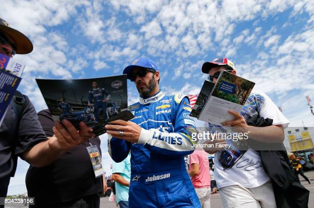 Jimmie Johnson driver of the Lowe's Chevrolet signs autographs for fans in the garage area during practice for the Monster Energy NASCAR Cup Series...