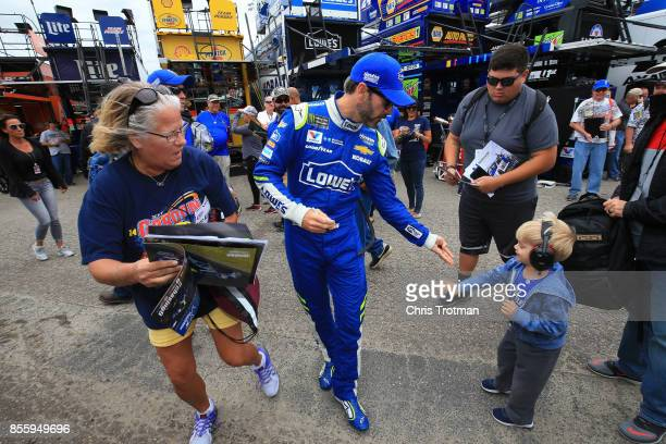 Jimmie Johnson driver of the Lowe's Chevrolet signs autographs for fans during practice for the Monster Energy NASCAR Cup Series Apache Warrior 400...