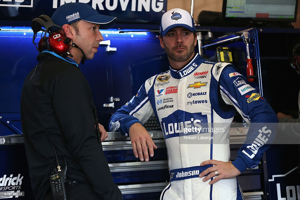Jimmie Johnson (right), driver of the #48 Lowe's Chevrolet, speaks with crew chief Chad Knaus during practice for the NASCAR Sprint Cup Series Auto Club 400 at Auto Club Speedway on March 21, 2014 in Fontana, California.