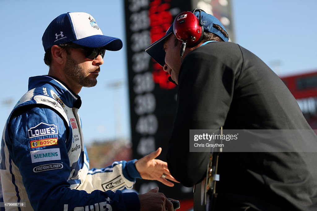 Jimmie Johnson, driver of the #48 Lowe's Chevrolet, speaks with crew chief Chad Knaus during qualifying for the NASCAR Sprint Cup Series Auto Club 400 at Auto Club Speedway on March 21, 2014 in Fontana, California.