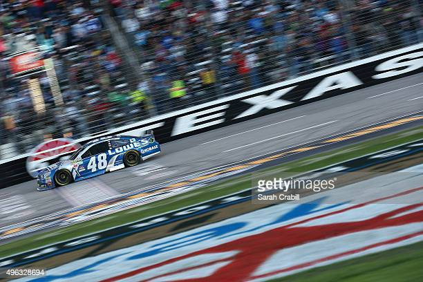 Jimmie Johnson driver of the Lowe's Chevrolet takes the checkered flag to win the NASCAR Sprint Cup Series AAA Texas 500 at Texas Motor Speedway on...