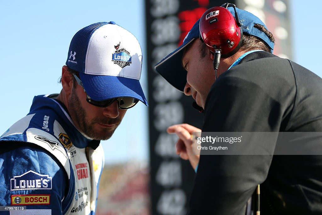 Jimmie Johnson (left), driver of the #48 Lowe's Chevrolet, talks with crew chief Chad Knaus during qualifying for the NASCAR Sprint Cup Series Auto Club 400 at Auto Club Speedway on March 21, 2014 in Fontana, California.