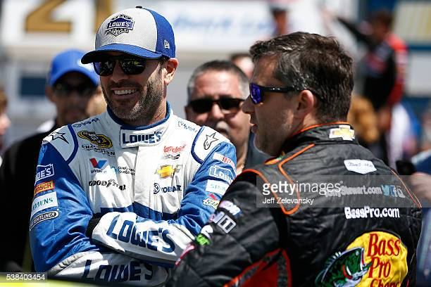 Jimmie Johnson driver of the Lowe's Chevrolet talks with Tony Stewart driver of the Bass Pro Shops/TRACKER Boats Chevrolet on the grid prior to the...