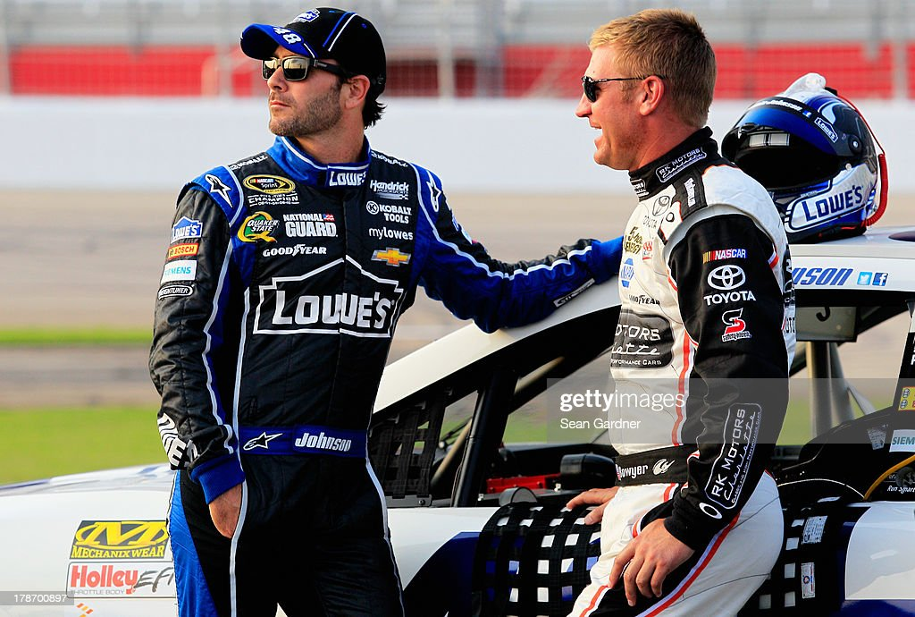 Jimmie Johnson, driver of the #48 Lowe's Dover White Chevrolet, and Clint Bowyer, driver of the #15 RKMotorsCharlotte.com Toyota, talk while standing on the grid during qualifying for the NASCAR Sprint Cup Series AdvoCare 500 at Atlanta Motor Speedway on August 30, 2013 in Hampton, Georgia.