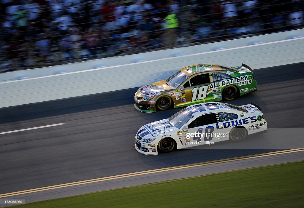 Jimmie Johnson, driver of the #48 Lowe's Dover White Chevrolet, and Kyle Busch, driver of the #18 Interstate Batteries Toyota, race during the NASCAR Sprint Cup Series Coke Zero 400 at Daytona International Speedway on July 6, 2013 in Daytona Beach, Florida..