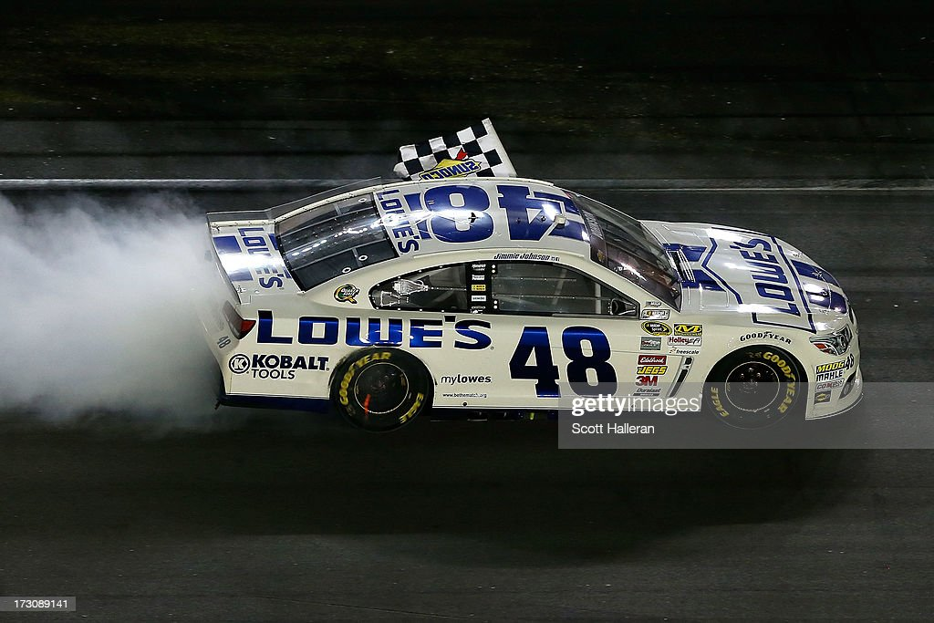 Jimmie Johnson, driver of the #48 Lowe's Dover White Chevrolet, celebrates with the checkered flag as he performs a burnout after winning the NASCAR Sprint Cup Series Coke Zero 400 at Daytona International Speedway on July 6, 2013 in Daytona Beach, Florida.