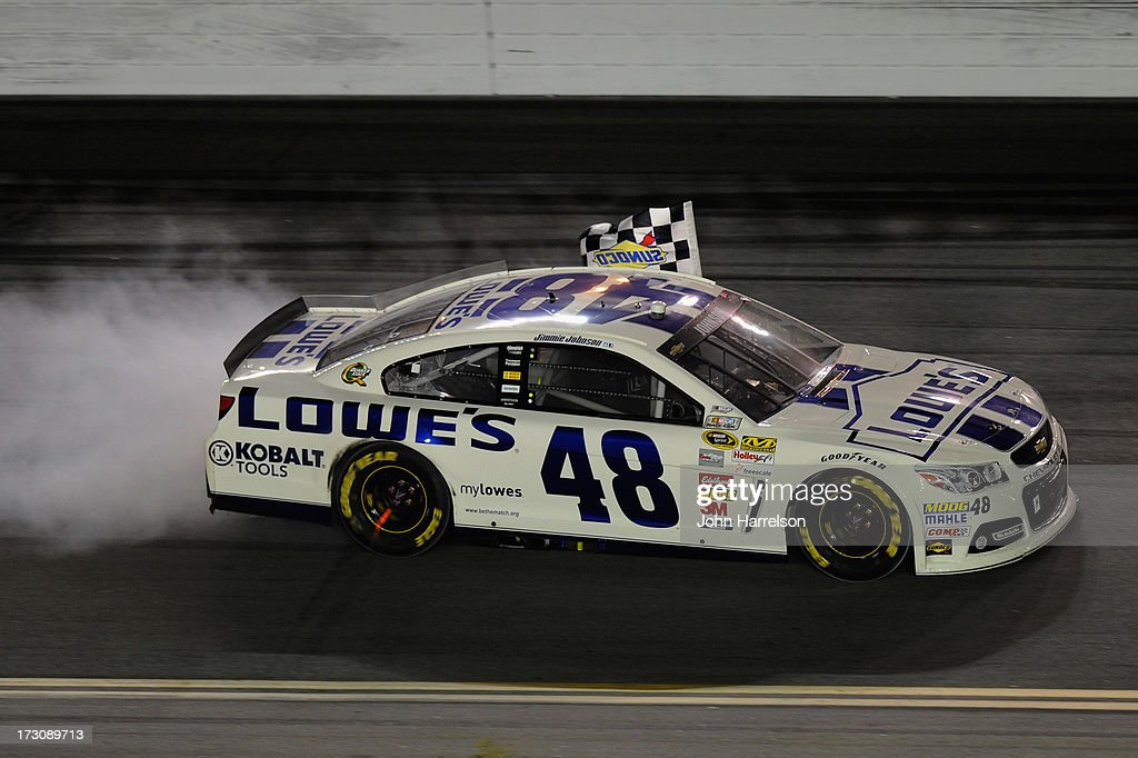 Jimmie Johnson, driver of the #48 Lowe's Dover White Chevrolet, celebrates with the Sunoco checkered flag as he performs a burout in celebration of winning the NASCAR Sprint Cup Series Coke Zero 400 at Daytona International Speedway on July 6, 2013 in Daytona Beach, Florida.