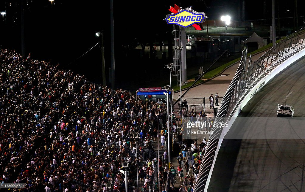 Jimmie Johnson, driver of the #48 Lowe's Dover White Chevrolet, celebrates with the SUnoco checkered flag after winning the NASCAR Sprint Cup Series Coke Zero 400 at Daytona International Speedway on July 6, 2013 in Daytona Beach, Florida.