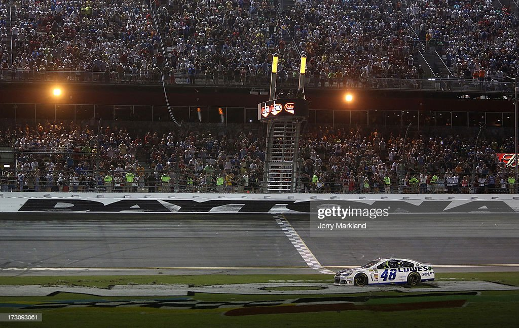 Jimmie Johnson, driver of the #48 Lowe's Dover White Chevrolet, celebrates in the infield grass after winning the NASCAR Sprint Cup Series Coke Zero 400 at Daytona International Speedway on July 6, 2013 in Daytona Beach, Florida.
