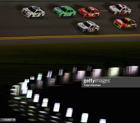 Jimmie Johnson driver of the Lowe's Dover White Chevrolet leads Danica Patrick driver of the GoDaddycom Chevrolet Jamie McMurray driver of the Cessna...