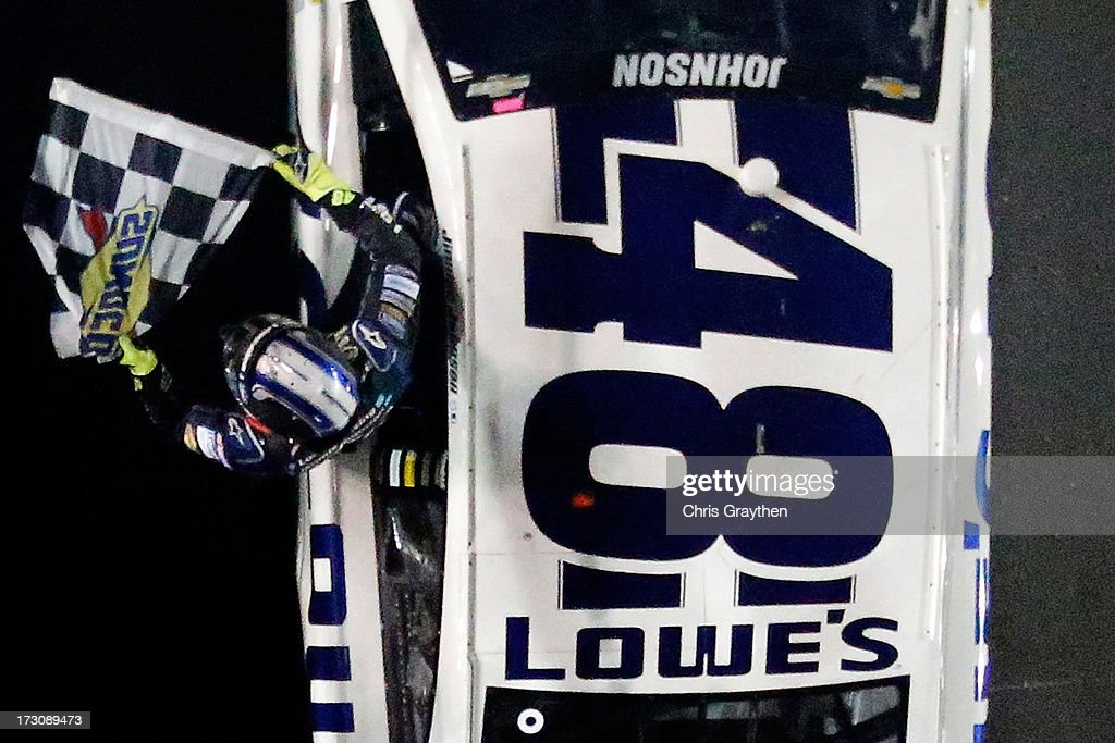 Jimmie Johnson, driver of the #48 Lowe's Dover White Chevrolet, waves the checkered flag to celebrate winning the NASCAR Sprint Cup Series Coke Zero 400 at Daytona International Speedway on July 6, 2013 in Daytona Beach, Florida.