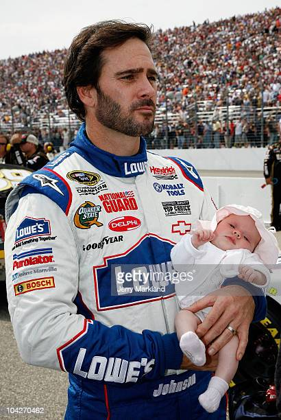 Jimmie Johnson driver of the Lowe's / Johns Manville Chevrolet holds his baby daughter Genevieve Marie as he stands on the grid prior to the start of...