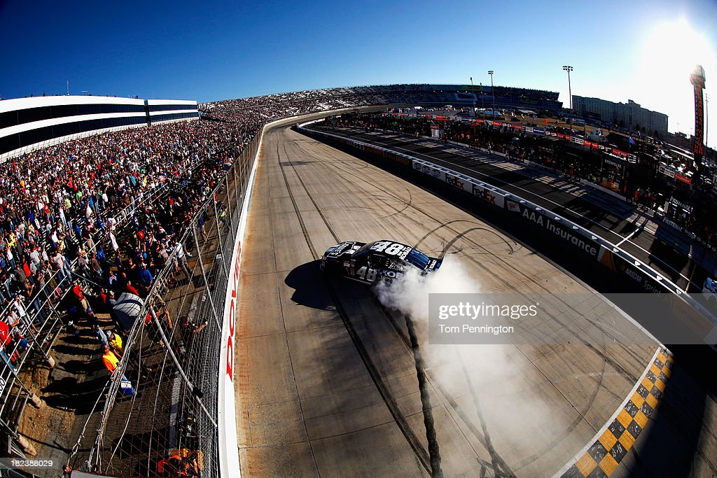 Jimmie Johnson, driver of the #48 Lowe's / Kobalt Tools Chevrolet, celebrates with a burnout after winning during the NASCAR Sprint Cup Series AAA 400 at Dover International Speedway on September 29, 2013 in Dover, Delaware.