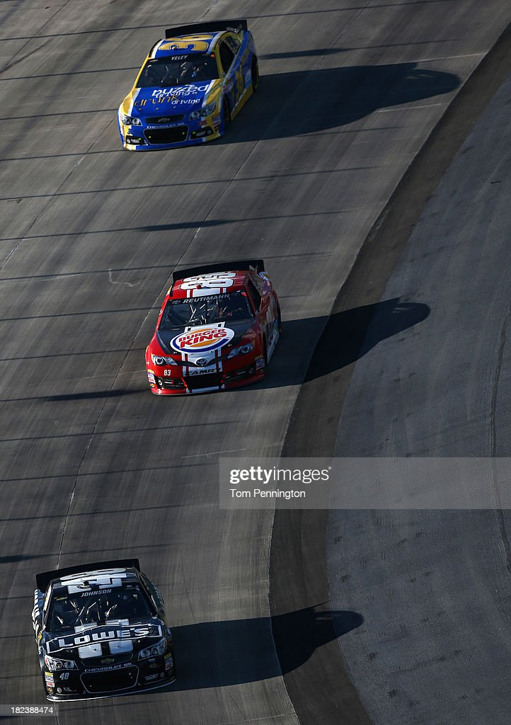 Jimmie Johnson, driver of the #48 Lowe's / Kobalt Tools Chevrolet, leads David Reutimann, driver of the #83 Burger King / Dr. Pepper Toyota, and J.J. Yeley, driver of the #36 Drive Sober Arrive Alive Chevrolet, during the NASCAR Sprint Cup Series AAA 400 at Dover International Speedway on September 29, 2013 in Dover, Delaware.