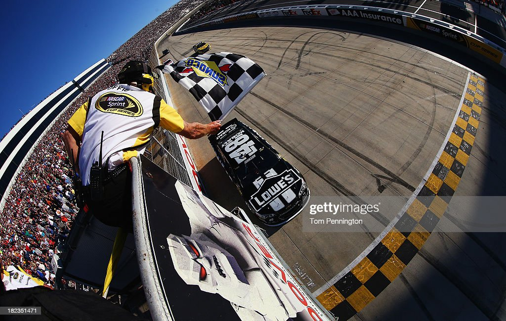 Jimmie Johnson, driver of the #48 Lowe's / Kobalt Tools Chevrolet, takes the checkered flag to win the NASCAR Sprint Cup Series AAA 400 at Dover International Speedway on September 29, 2013 in Dover, Delaware.