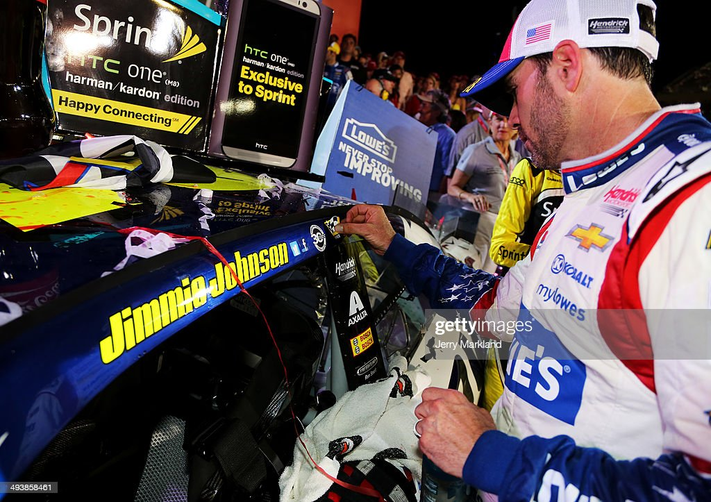 Jimmie Johnson, driver of the #48 Lowe's Patriotic Chevrolet, places the winner's decal on his car after winning the NASCAR Sprint Cup Series Coca-Cola 600 at Charlotte Motor Speedway on May 25, 2014 in Charlotte, North Carolina.