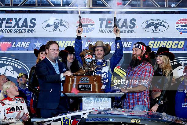 Jimmie Johnson driver of the Lowe's Pro Services Chevrolet celebrates with pistols in Victory Lane after winning the NASCAR Sprint Cup Series Duck...
