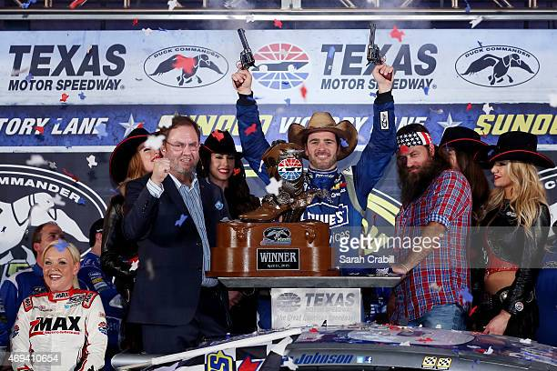 Jimmie Johnson driver of the Lowe's Pro Services Chevrolet celebrates with pistols presented by Texas Motor Speedway President Eddie Gossage left in...