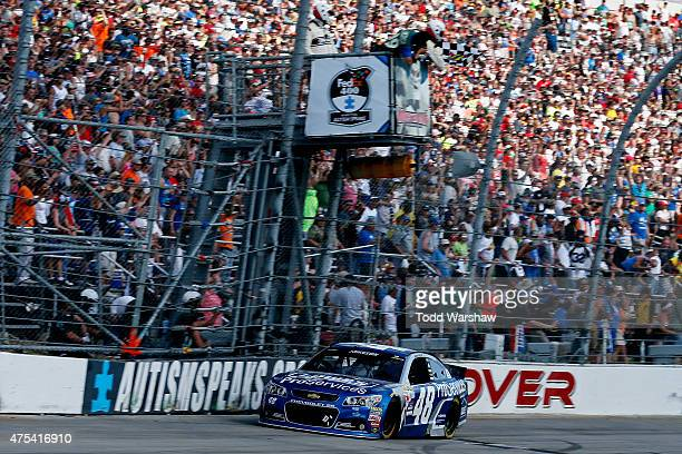Jimmie Johnson driver of the Lowe's Pro Services Chevrolet crosses the finish line to win the NASCAR Sprint Cup Series FedEx 400 Benefiting Autism...