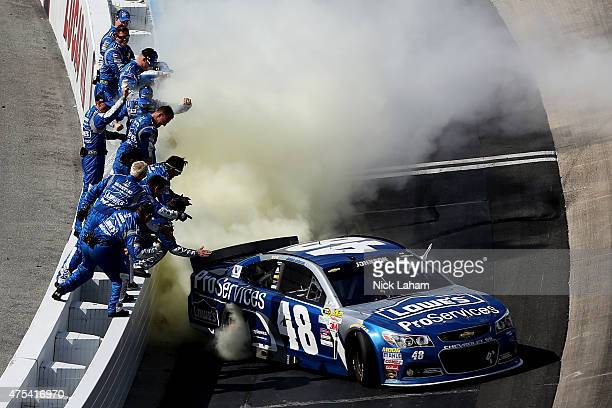 Jimmie Johnson driver of the Lowe's Pro Services Chevrolet is cheered by his team while celebrating with a burnout after winning the NASCAR Sprint...