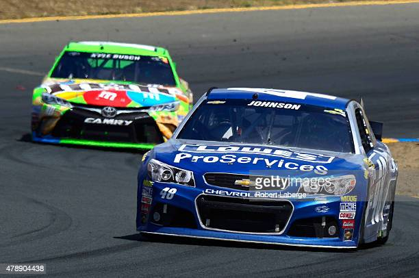 Jimmie Johnson driver of the Lowe's Pro Services Chevrolet leads Kyle Busch driver of the MM's Crispy Toyota during the NASCAR Sprint Cup Series...