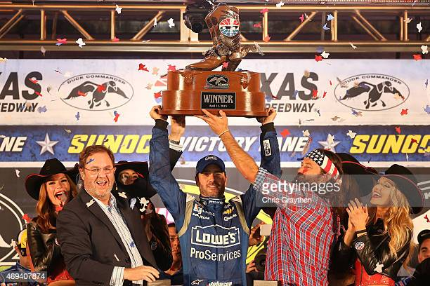 Jimmie Johnson driver of the Lowe's Pro Services Chevrolet lifts the winner's trophy presented by Texas Motor Speedway President Eddie Gossage left...