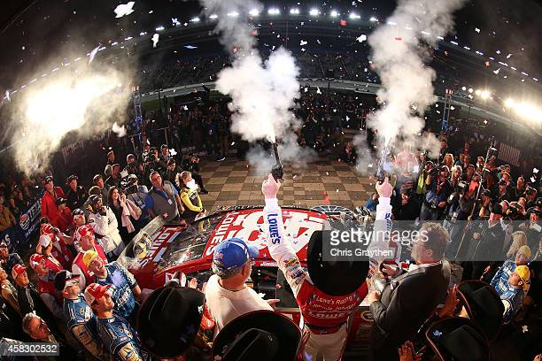 Jimmie Johnson driver of the Lowe's Red Vest Chevrolet celebrates in Victory Lane with pistols after winning the NASCAR Sprint Cup Series AAA Texas...