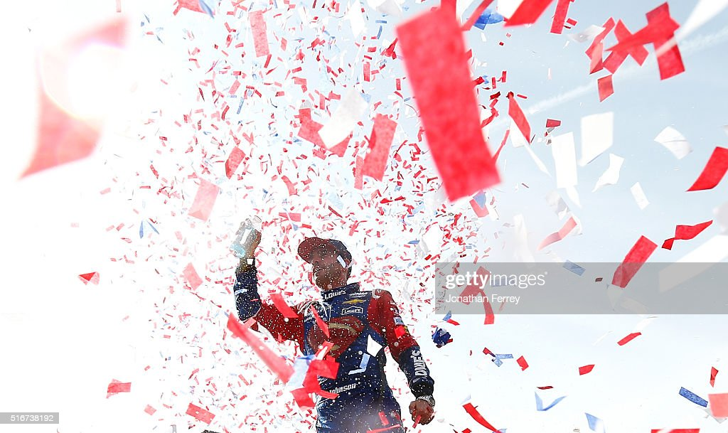 Jimmie Johnson driver of the Lowe's / Superman Chevrolet celebrates in victory lane after winning the NASCAR Sprint Cup Series Auto Club 400 at Auto...