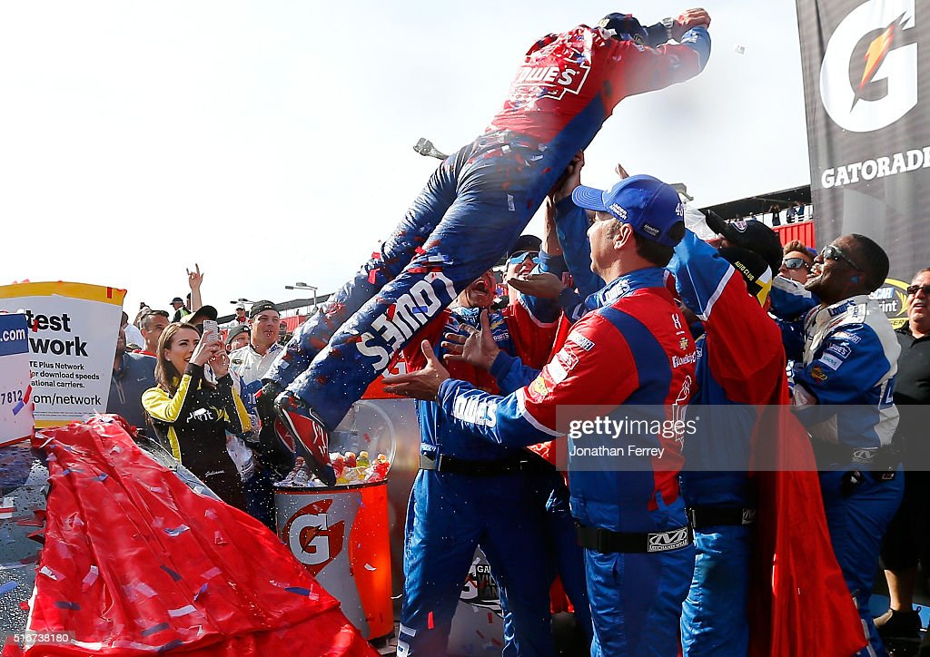 Jimmie Johnson driver of the Lowe's / Superman Chevrolet dives into his crew members in victory lane after winning the NASCAR Sprint Cup Series Auto...