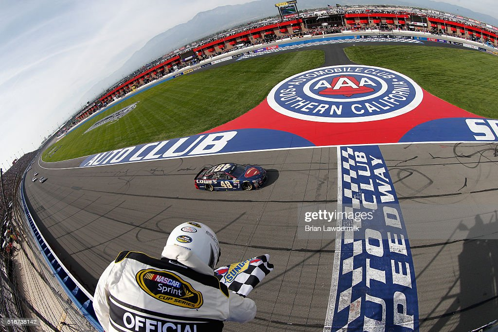 Jimmie Johnson driver of the Lowe's / Superman Chevrolet takes the checkered flag to win the NASCAR Sprint Cup Series Auto Club 400 at Auto Club...