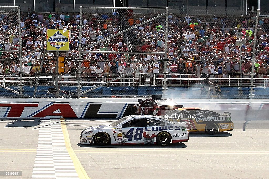 Jimmie Johnson, driver of the #48 Lowe's / Valspar Reserve Chevrolet, and Ryan Newman, driver of the #31 Caterpillar Chevrolet, cross the finish line as Alex Bowman, driver of the #23 Dr. Pepper Toyota, goes into the wall during the NASCAR Sprint Cup Series Aaron's 499 at Talladega Superspeedway on May 4, 2014 in Talladega, Alabama.
