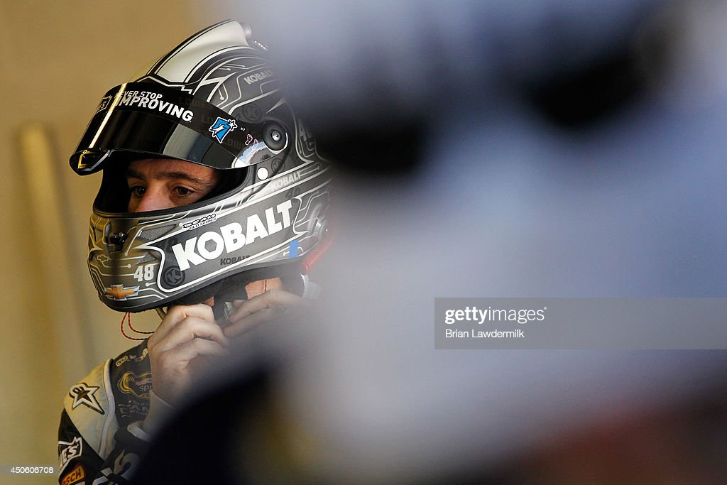 Jimmie Johnson, driver of the #48 Lowe's/Kobalt Tools Chevrolet, adjusts his helmet in the garage area during practice for the NASCAR Sprint Cup Series Quicken Loans 400 at Michigan International Speedway on June 14, 2014 in Brooklyn, Michigan.