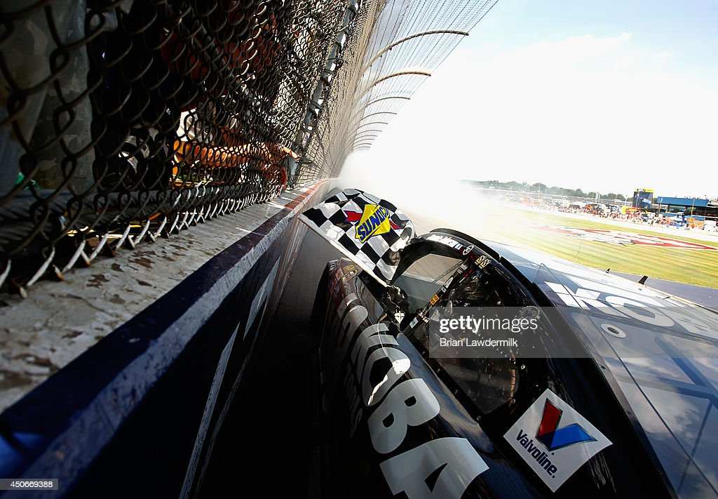 Jimmie Johnson, driver of the #48 Lowe's/Kobalt Tools Chevrolet, celebrates with the checkered flag after winning the NASCAR Sprint Cup Series Quicken Loans 400 at Michigan International Speedway on June 15, 2014 in Brooklyn, Michigan.