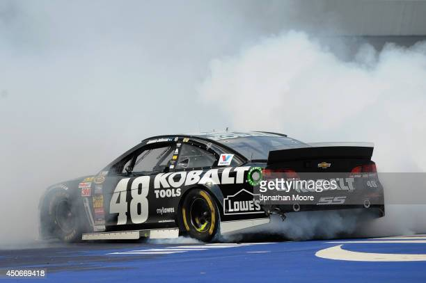 Jimmie Johnson driver of the Lowe's/Kobalt Tools Chevrolet celebrates with a burnout after winning the NASCAR Sprint Cup Series Quicken Loans 400 at...