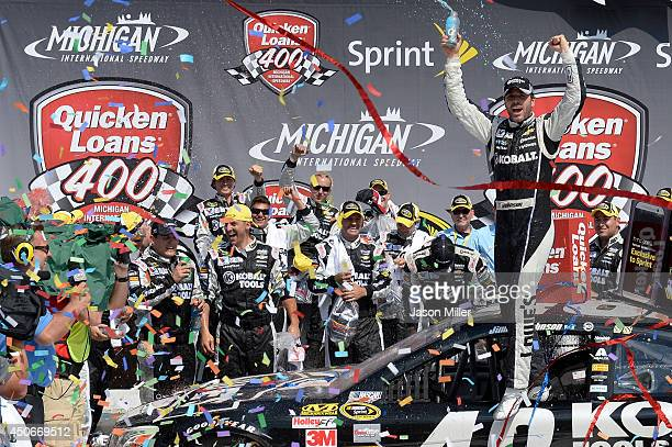 Jimmie Johnson driver of the Lowe's/Kobalt Tools Chevrolet celebrates in Victory Lane after winning the NASCAR Sprint Cup Series Quicken Loans 400 at...