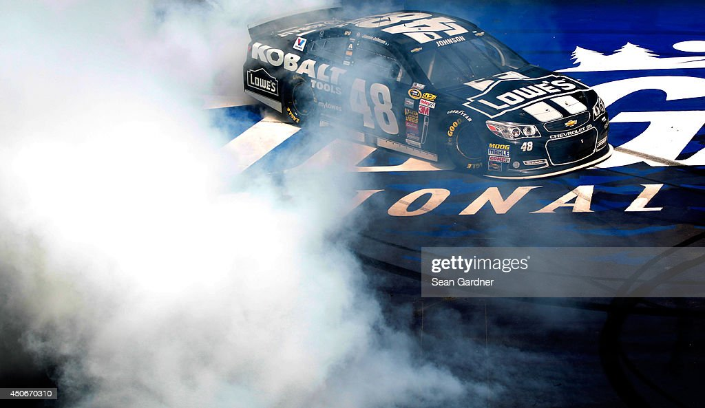 Jimmie Johnson, driver of the #48 Lowe's/Kobalt Tools Chevrolet, celebrates with a burnout after winning the NASCAR Sprint Cup Series Quicken Loans 400 at Michigan International Speedway on June 15, 2014 in Brooklyn, Michigan.