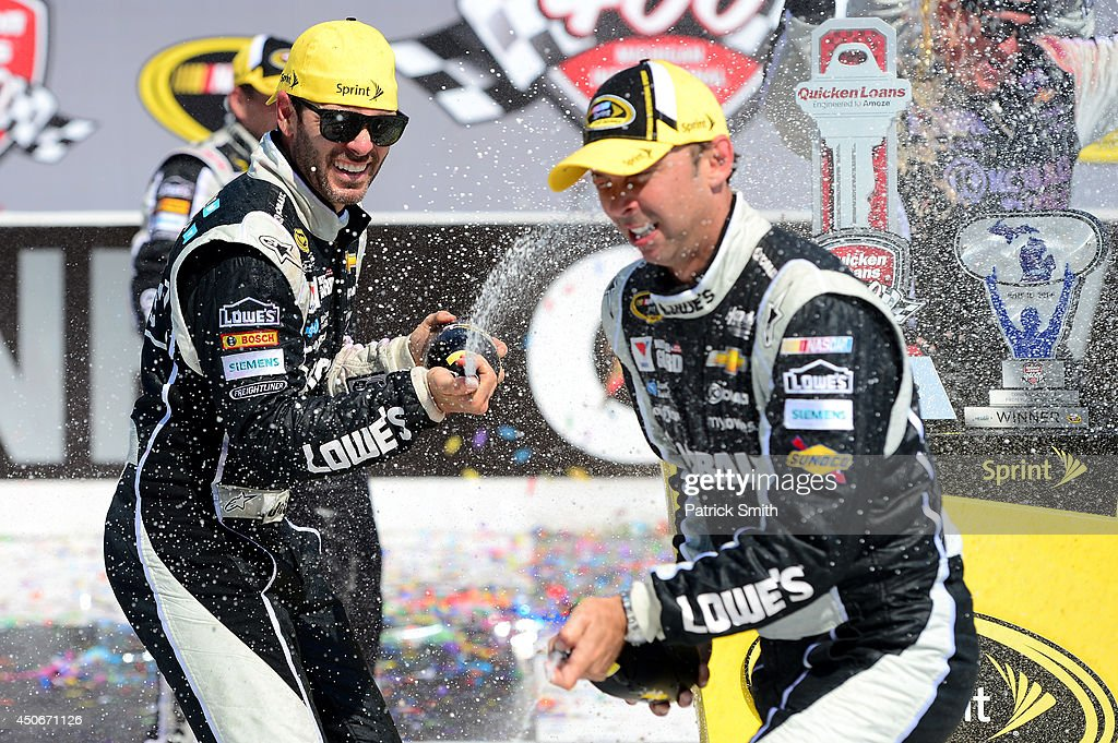 Jimmie Johnson (left), driver of the #48 Lowe's/Kobalt Tools Chevrolet, celebrates with his crew chief Chad Knaus in Victory Lane after winning the NASCAR Sprint Cup Series Quicken Loans 400 at Michigan International Speedway on June 15, 2014 in Brooklyn, Michigan.