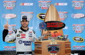 Jimmie Johnson driver of the Lowe's/Kobalt Tools Chevrolet celebrates in victory lane with the trophy after winning the NASCAR Sprint Cup Series Auto...