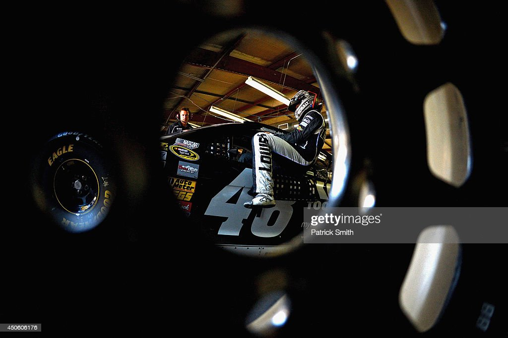 Jimmie Johnson, driver of the #48 Lowe's/Kobalt Tools Chevrolet, climbs into his car in the garage area during practice for the NASCAR Sprint Cup Series Quicken Loans 400 at Michigan International Speedway on June 14, 2014 in Brooklyn, Michigan.