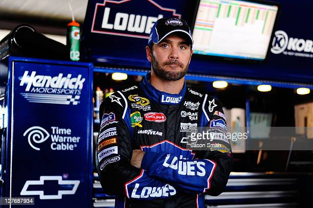 Jimmie Johnson driver of the Lowe's/Kobalt Tools Chevrolet looks on from the garage area during practice for the NASCAR Sprint Cup Series AAA 400 at...