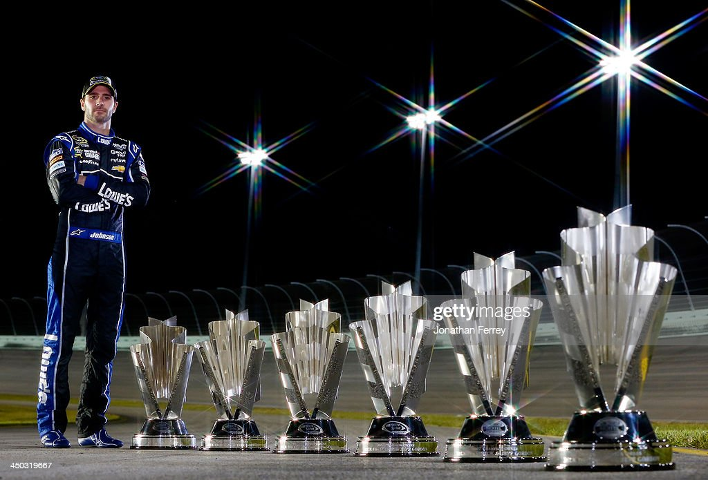 Jimmie Johnson, driver of the #48 Lowe's/Kobalt Tools Chevrolet, poses with his series championship trophies after the NASCAR Sprint Cup Series Ford EcoBoost 400 at Homestead-Miami Speedway on November 17, 2013 in Homestead, Florida.