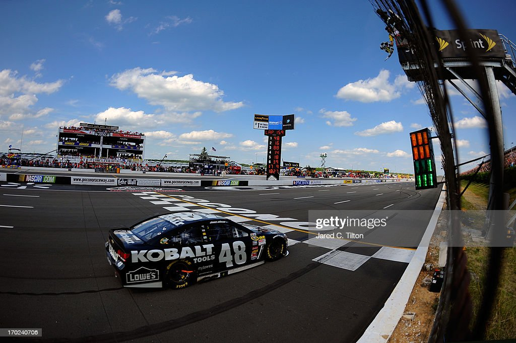 Jimmie Johnson, driver of the #48 Lowe's/Kobalt Tools Chevrolet, races to the finishline to win the NASCAR Sprint Cup Series Party in the Poconos 400 at Pocono Raceway on June 9, 2013 in Long Pond, Pennsylvania.