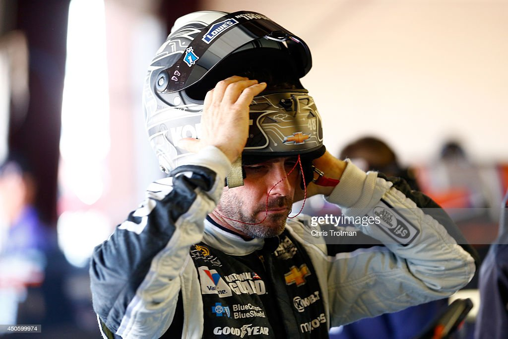 Jimmie Johnson, driver of the #48 Lowe's/Kobalt Tools Chevrolet, removes his helmet in the garage area during practice for the NASCAR Sprint Cup Series Quicken Loans 400 at Michigan International Speedway on June 14, 2014 in Brooklyn, Michigan.