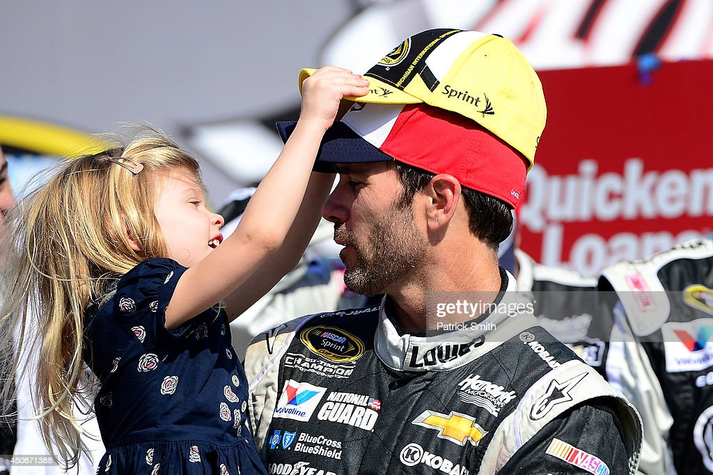 Jimmie Johnson, driver of the #48 Lowe's/Kobalt Tools Chevrolet, shares a moment with his daughter Genevieve in Victory Lane after winning the NASCAR Sprint Cup Series Quicken Loans 400 at Michigan International Speedway on June 15, 2014 in Brooklyn, Michigan.