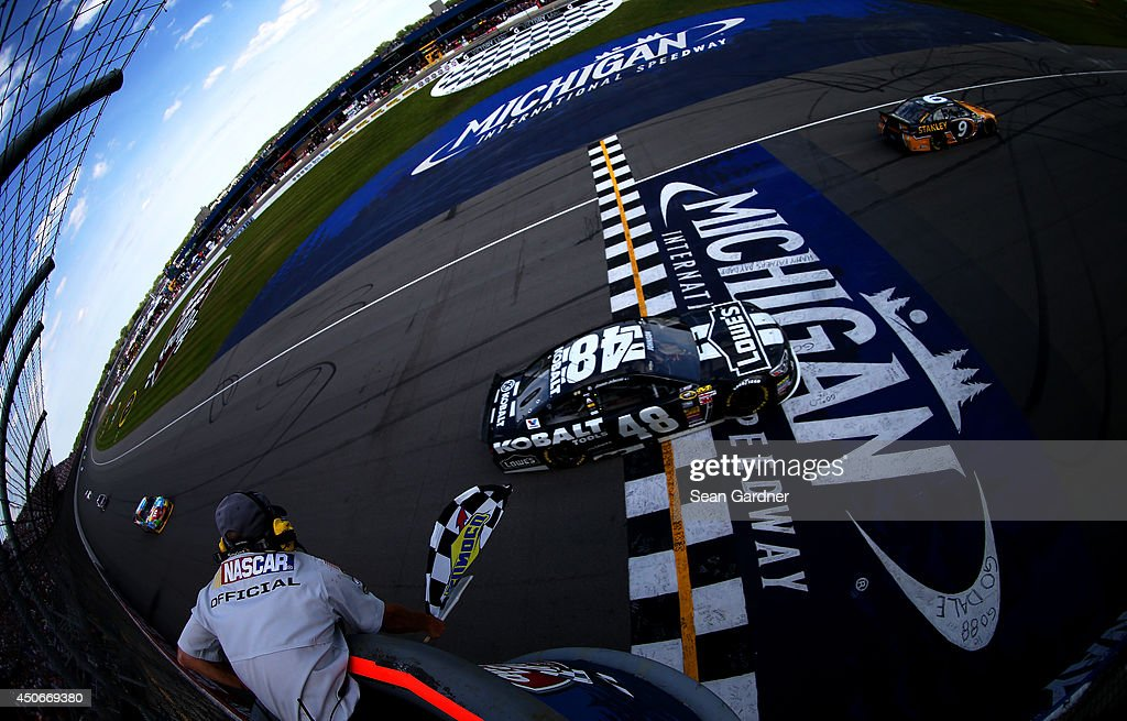 Jimmie Johnson, driver of the #48 Lowe's/Kobalt Tools Chevrolet, takes the checkered flag to win the NASCAR Sprint Cup Series Quicken Loans 400 at Michigan International Speedway on June 15, 2014 in Brooklyn, Michigan.