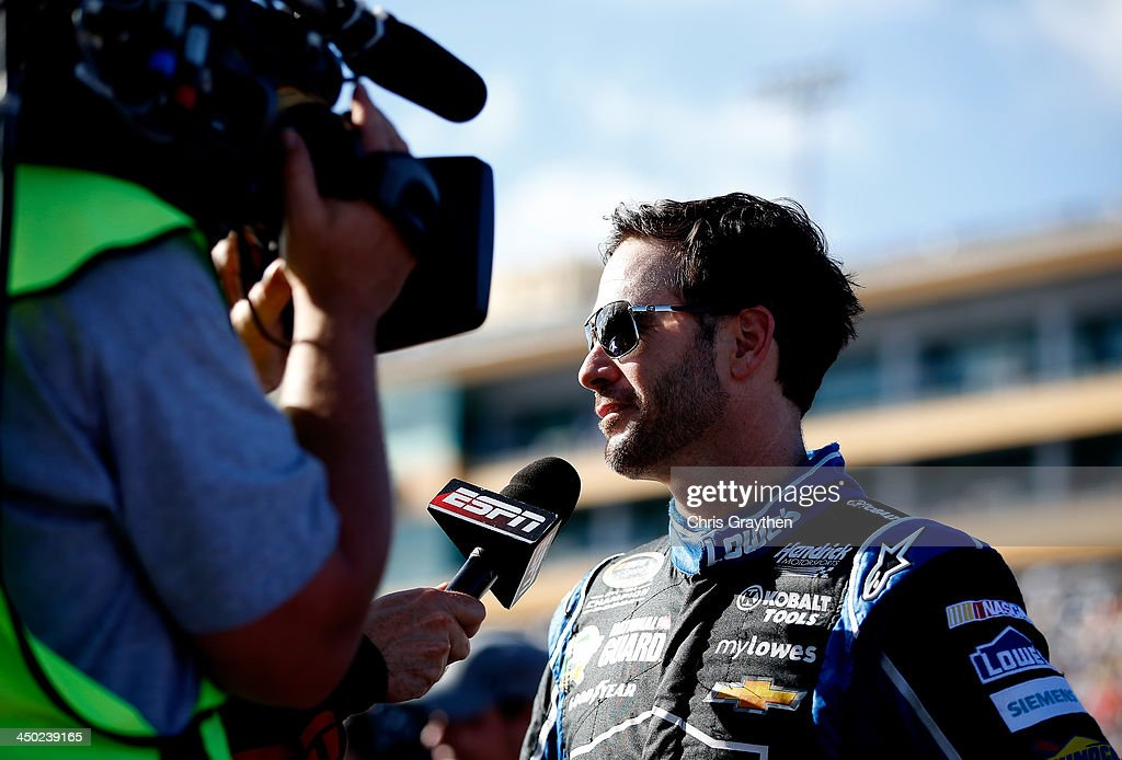Jimmie Johnson, driver of the #48 Lowe's/Kobalt Tools Chevrolet, talks to the media on the grid prior to the NASCAR Sprint Cup Series Ford EcoBoost 400 at Homestead-Miami Speedway on November 17, 2013 in Homestead, Florida.
